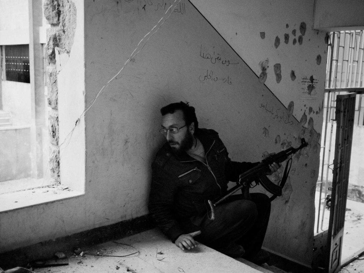 Aleppo, Syria. March, 2013. A rebel fighter takes cover inside a school during fighting between rebel forces and regime soldiers in Aleppo.
